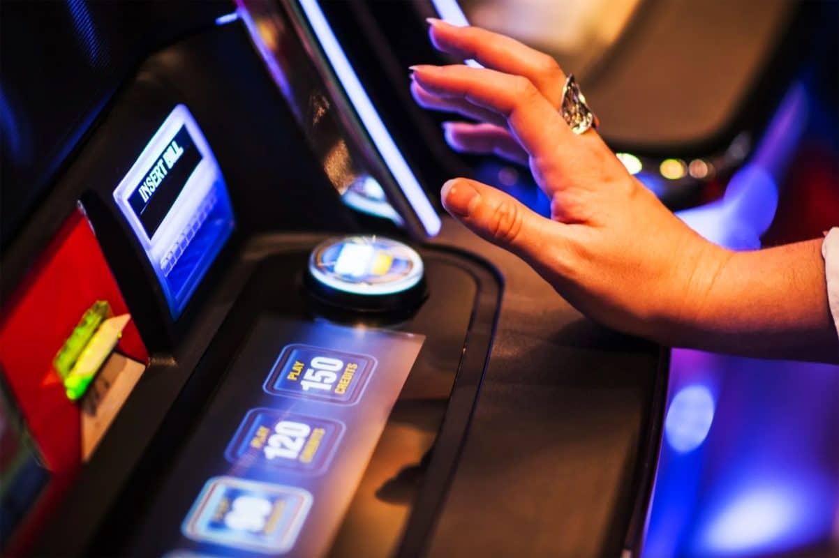 Frau spielt an einem Glücksspielautomaten